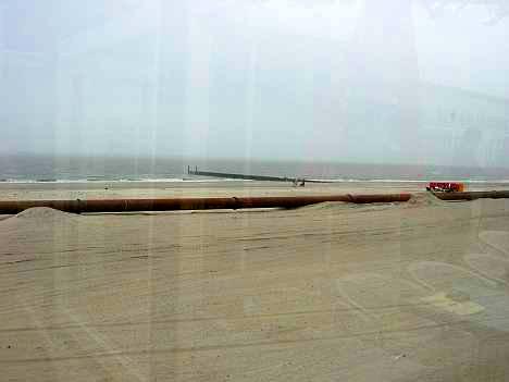Op het strand, spiegeling door ruit van strandpaviljoen © copyright dutchmarco